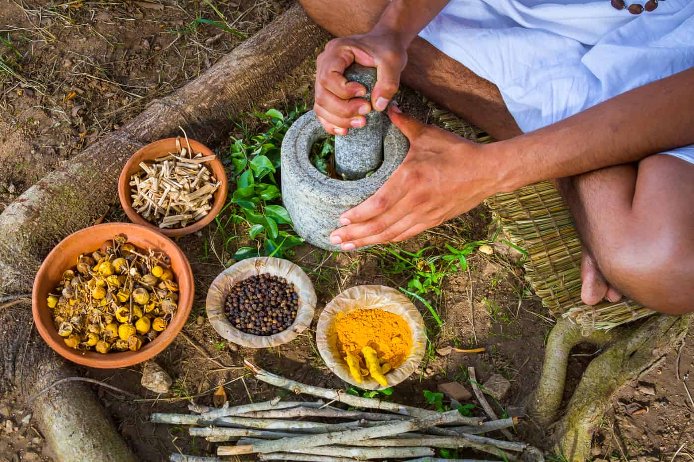 A young man preparing ayurvedic medicine in the traditional mann