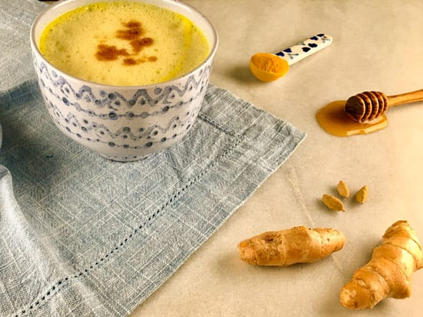 healthy turmeric milk with ginger, cardamom and honey